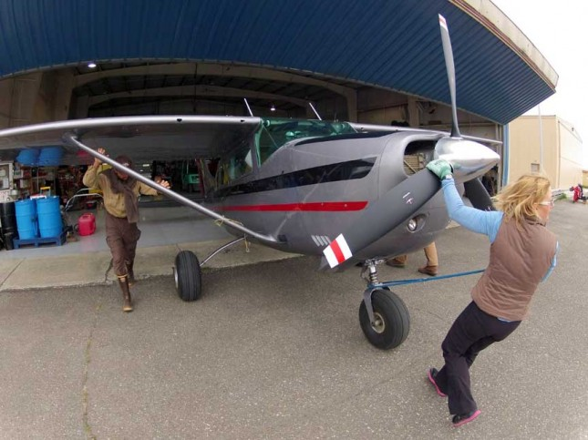 Pilot Heather pulls a Cessna 206 equipped with tundra tires out of the Egli Air Haul hanger.